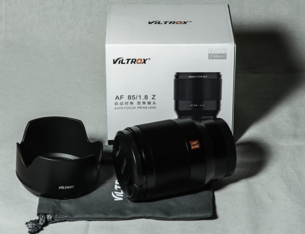VILTROX OBJEKTIV AF 85 MM F/1.8 MIT NIKON Z-MOUNT Produktbild mit Verpackung im Hintergrund