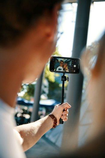 Blick ueber die Schulter: Paerchen macht Selfie mit Smartphone auf VACUUM mini triopod von FIDLOCK