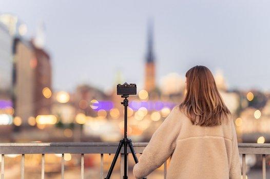 Szenebild: Fotografin mit Kamera auf Velbon-Stativ vor unscharfer Stadtkulisse