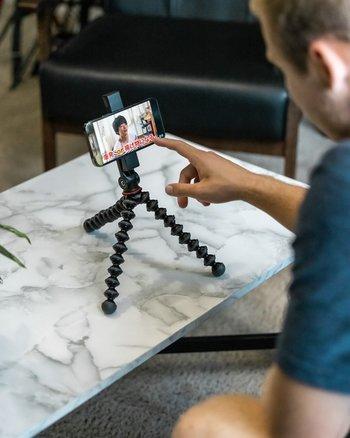 Mann bedient Smaprtphone mit GripTight GorillaPod für MagSafe auf niedrigem Tisch
