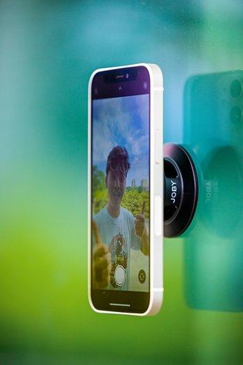 Smartphone mit GripTight Wandhalterung für MagSafe von JOBY an glatter Oberfläche befestigt.