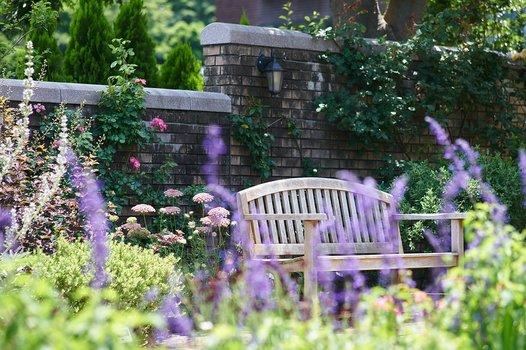 Bank im Garten, im Vordergrund Blumenbeete